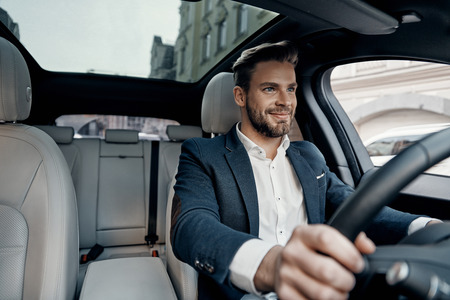 Success in motion. Handsome young man in full suit smiling while driving a car 版權商用圖片 - 93926898