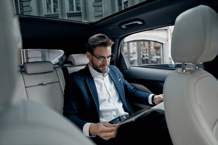Reading latest news. Handsome young man in full suit reading a newspaper while sitting in the car Stok Fotoğraf - 93926900