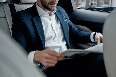 Latest business news. Close up of young man in full suit reading a newspaper while sitting in the car