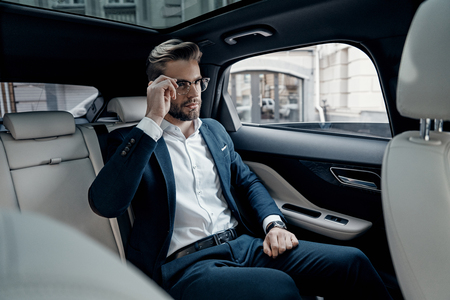 Always confident. Handsome young man in full suit adjusting his eyewear while sitting in the car Stok Fotoğraf - 93926910
