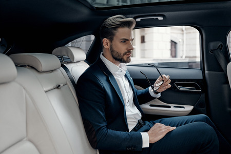 Confident businessman. Handsome young man in full suit looking away while sitting in the car