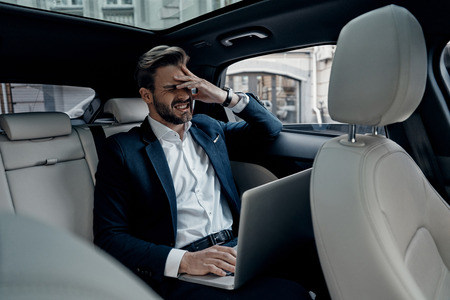 Oh no! Frustrated young man in full suit working using laptop and covering face with hand while sitting in the car