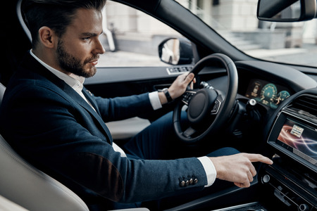 On the way to business meeting. Handsome young man in full suit pushing buttons while driving a car Banco de Imagens - 93878298