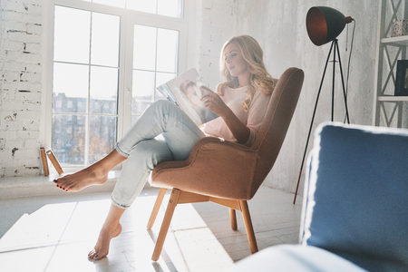 Beautiful young woman reading a magazine while sitting in the armchair at home