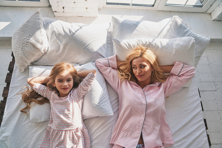 Sunday morning. Top view of young beautiful mother and her cute daughter keeping hands behind head and smiling while lying on the bed at home Stok Fotoğraf