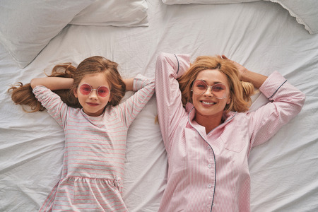 Simply being around. Top view of young beautiful mother and her cute daughter keeping hands behind head and smiling while lying on the bed at home Stok Fotoğraf