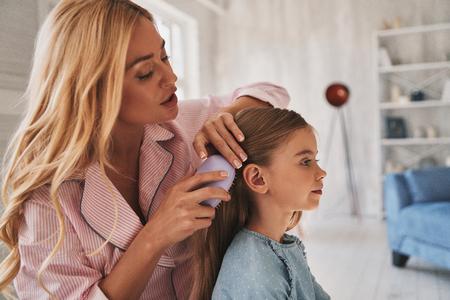 그녀의 공주 돌보는 중. 집에서 침대에 앉아있는 동안 그녀의 딸 머리를 솔 질하는 아름 다운 젊은 어머니 스톡 콘텐츠