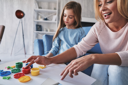 Their common hobby. Mother and daughter painting with fingers and smiling while spending time at home Banco de Imagens