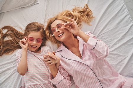 Best friends. Top view of young beautiful mother and her cute daughter wearing eyewear and smiling while lying on the bed at home