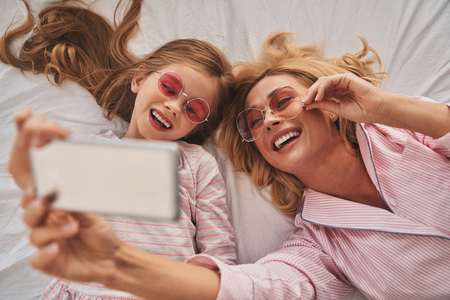 Smile! Top view of young beautiful mother and her cute daughter taking selfie with smart phone and smiling while lying on the bed at home