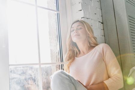 穏やかで幸せな気持ち。魅力的な若い女性は、自宅の窓枠に座っている間、目を閉じて微笑んでいる