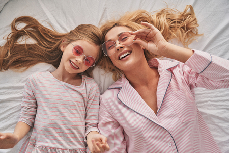Happy together. Top view of young beautiful mother and her cute daughter wearing eyewear and smiling while lying on the bed at home Stok Fotoğraf