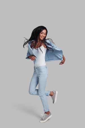 Feeling comfortable in her style. Full length studio shot of attractive young woman in casual wear smiling while jumping against grey background Stock Photo