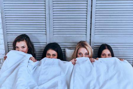 Horrorfilm kijken. Hoogste mening van vier mooie jonge vrouwen die gezicht behandelen met witte deken en camera bekijken terwijl het liggen in het bed Stockfoto