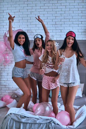 Feeling so happy! Full length of four attractive young smiling women in pajamas toasting each other while having a slumber party in the bedroom with balloons all over the place Imagens