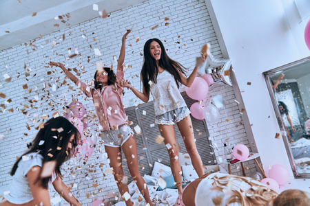 So much fun! Four attractive young women in pajamas smiling and gesturing while jumping in the bedroom with confetti flying everywhere