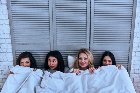 Time to sleep.  Top view of four beautiful young women covering with white blanket and smiling while lying in the bed