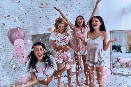 ¡Si! Cuatro atractivas mujeres jóvenes en pijama sonriendo y gesticulando mientras saltan en la habitación con confeti volando por todas partes Foto de archivo