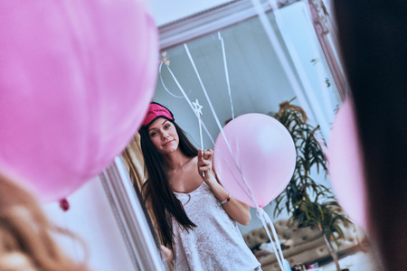 Amazing girl. Reflection of young attractive woman in night wear and sleep mask holding a balloon and smiling while standing in front of the mirror