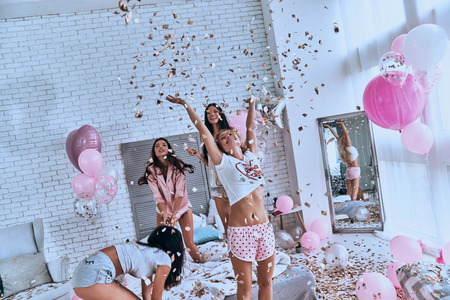 So happy! Four attractive young women in pajamas smiling and gesturing while jumping in the bedroom with confetti flying everywhere Foto de archivo