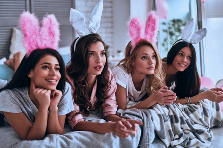 Pure beauties. Four attractive young women in bunny ears smiling and looking away while lying on the bed Stock Photo