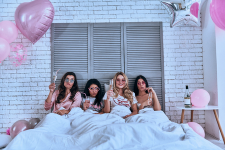 So much fun! Four attractive young women in pajamas drinking cocktails while lying in the bed with balloons all over the room Stock Photo