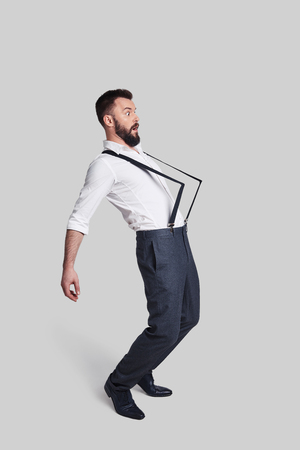 What is happening? Full length of surprised young man in suspenders pulled by something while standing against grey background