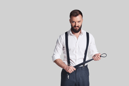 So cruel! Angry young man in formalwear carrying a belt and looking at camera while standing against grey background