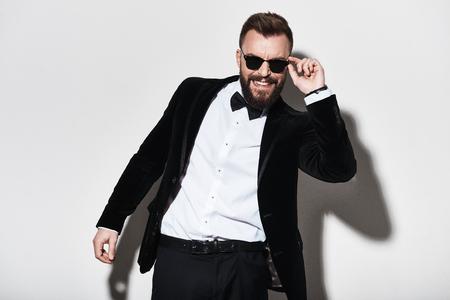 Man van charisma. Knappe jonge zijn in brillen aanpassen en mens die terwijl status tegen grijze achtergrond glimlachen