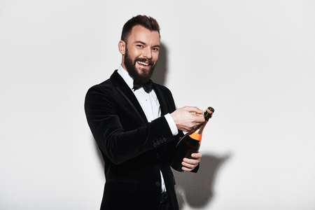 Little party never killed anybody. Handsome young man in full suit opening a bottle of champagne and smiling while standing against grey background