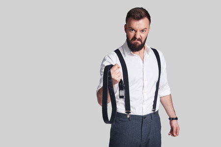 Dangerous man. Angry young man in formalwear carrying a belt and looking at camera while standing against grey background Stock Photo - 94611234