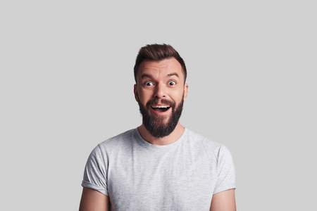 Good news. Shocked young man looking at camera and smiling while standing against grey background