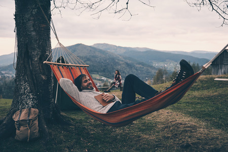 Handsome young man lying in hammock and smiling while camping with his girlfriend