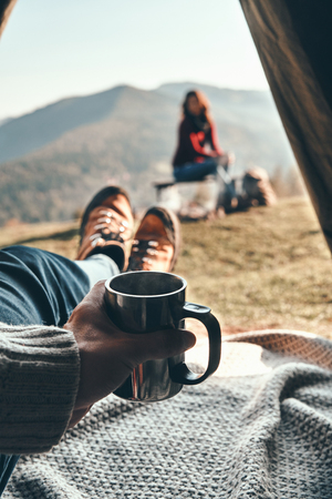 Lazy morning in mountains. Unrecognizable young man enjoying the view of mountain range from the tent while his girlfriend resting near the campfire