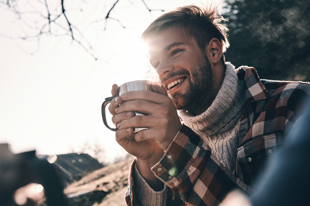 Handsome young man in warm clothing having morning coffee and smiling while camping in mountains Фото со стока