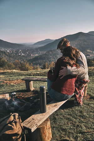 Beautiful young couple having morning coffee while spending carefree time in mountains Stock Photo