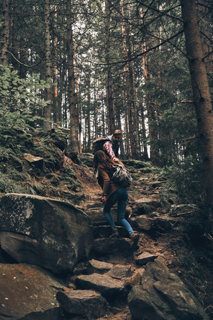 Full length of young couple holding hands and moving up while hiking together in the woods