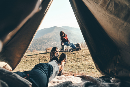 Woke up in the perfect place. Unrecognizable young man enjoying the view of mountain range from the tent while his girlfriend resting near the campfire