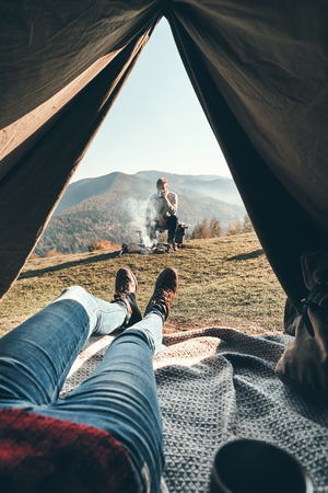 Woman enjoying the view of mountain range from the tent while her boyfriend resting near the campfire