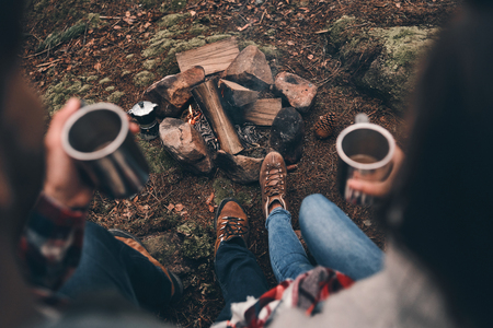 Just relaxing. Close up top view of young couple holding cups while warming up near the campfire