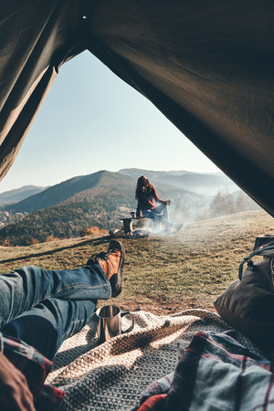 Unrecognizable young man enjoying the view of mountain range from the tent while his girlfriend resting near the campfire