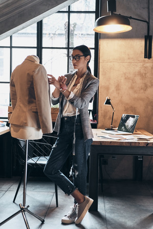 Successful fashion designer. Full length of serious young woman in eyewear using sewing needles for sewing a jacket on mannequin while standing in her workshop