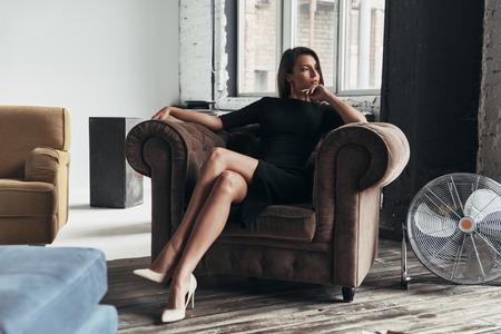 かなり熟考。エレガントな黒いドレスを着た魅力的な若い女性があごに手を置き、アームチェアに座りながら目をそらす