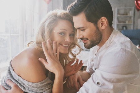 So happy! Beautiful young woman showing her engagement ring and smiling while sitting in the bedroom with her boyfriend Stock fotó