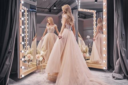 Schönes Kleid. In voller Länge vom attraktiven tragenden Hochzeitskleid der jungen Frau bei der Stellung vor dem Spiegel im Brautshop
