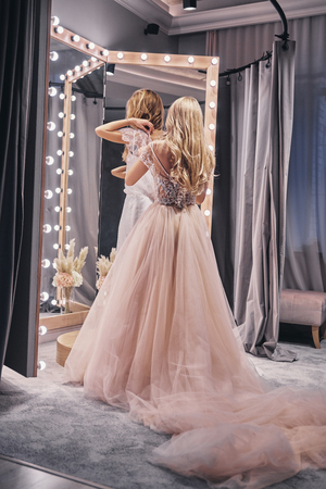 Fits perfect. Full length rear view of young woman adjusting a dress on her girlfriend while standing in the fitting room Stock Photo