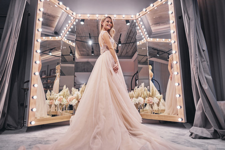 Exited about her wedding.  Full length of attractive young woman wearing wedding dress and smiling while standing in bridal shop