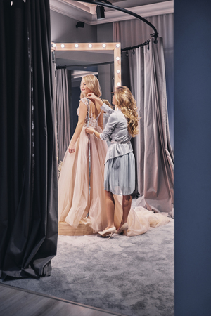 Everything must be perfect.  Full length of young woman measuring bride while standing in the fitting room Stock Photo