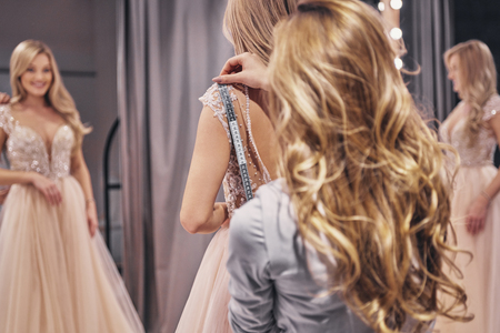 Young perfectionist.  Young woman measuring bride while standing in the fitting room