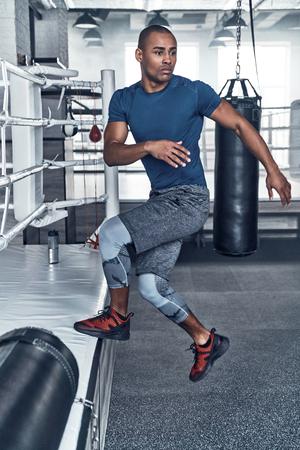Uit te werken. Knappe jonge Afrikaanse man in sportkleding springen tijdens het sporten in de sportschool